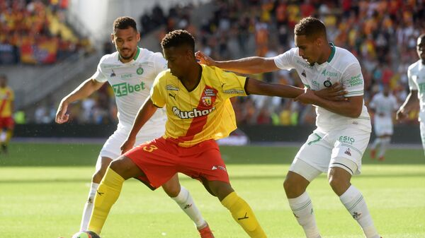 Lens's Bokote Banza and Saint Etienne's Yvann Macon fight for the ball during the French L1 football match between Lens and Saint-Etienne at the Bollaert Stadium in Lens, on August 15, 2021. (Photo by FRANCOIS LO PRESTI / AFP)