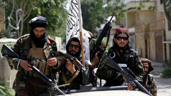 Боевики Талибана* с флагом во время патрулирования Кабула