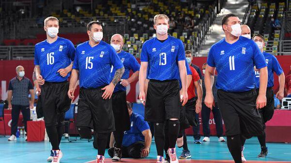 Российские спортсмены, члены сборной России (команда ПКР) перед началом матча предварительного этапа по волейболу сидя среди мужчин между сборными командами Японии и России на XVI Летних Паралимпийских играх в Токио.