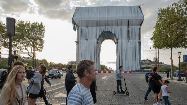 Люди идут мимо закрытой тканью Триумфальной арки в Париже