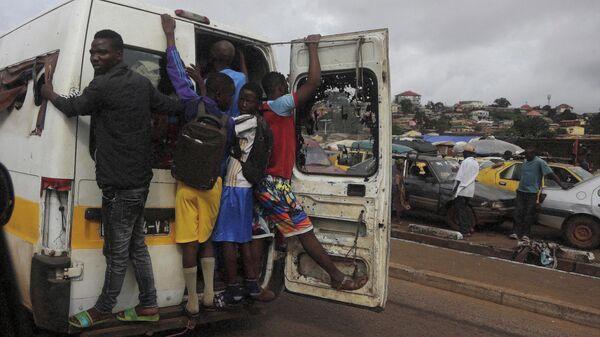 Местные жители едут в кузове грузовика в Конакри, Гвинея
