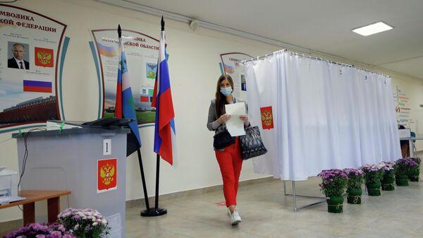 Девушка голосует на избирательном участке №196 в Белгороде