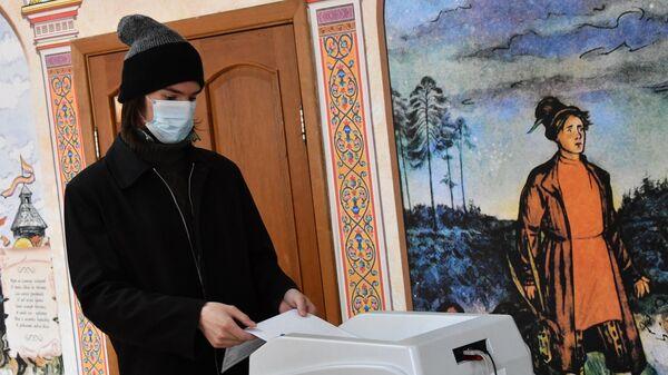 Молодой человек во время голосования на выборах депутатов Государственной Думы