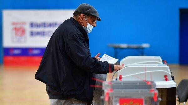 Мужчина голосует на выборах депутатов Государственной Думы РФ в Москве