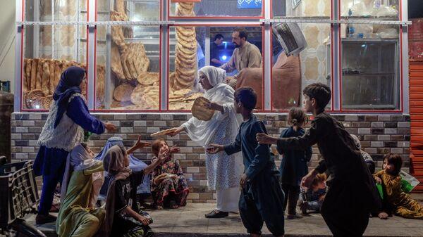 Женщина раздает хлеб нуждающимся возле пекарни в Кабуле