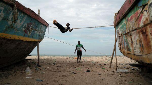 Дети играют на заваленном мусором пляже в Сенегале