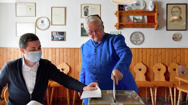 Женщина в традиционной одежде голосует на парламентских выборах в Кунневице, Германия