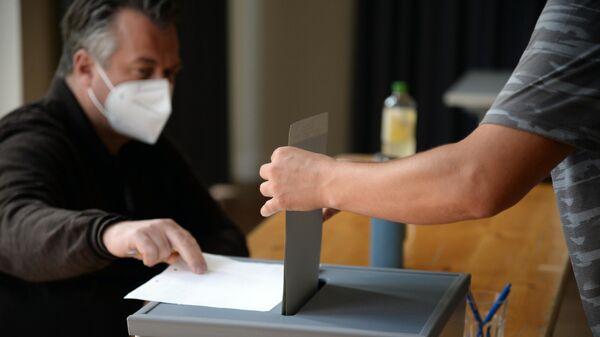 Мужчина опускает бюллетень в урну для голосования на одном из избирательных участков Потсдама во время голосования на выборах в Бундестаг