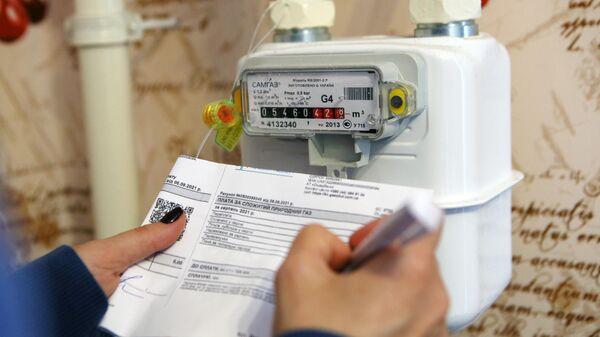 Девушка записывает показания счетчика учета газа у себя дома