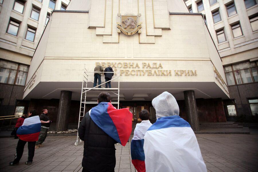 Рабочие снимают вывеску Верховной рады Автономной Республики Крым на украинском языке.