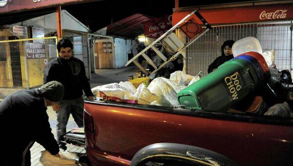 Жители собирают вещи и уходят из Талькауано, в котором объявлена тревога в связи с цунами.