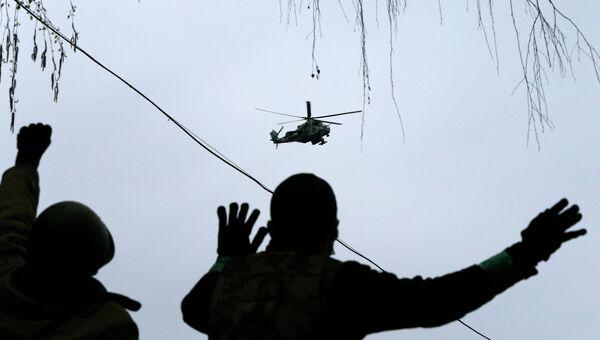Вертолет пролетает над людьми в Славянске 13 апреля 2014