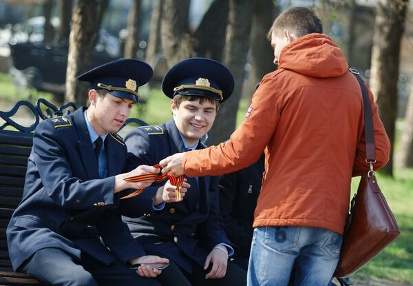 Волонтер раздает ленточки на площади у мемориала Вечный огонь Славы в Иркутске