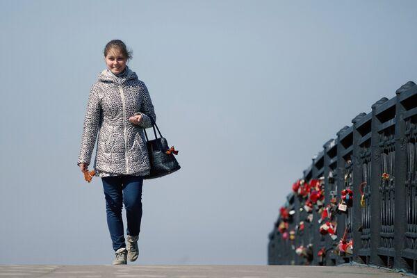 Девушка с ленточкой идет по пешеходному мосту через улицу Нижняя Набережная в Иркутске