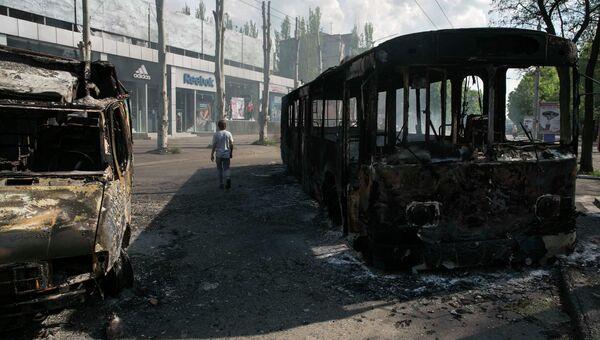 Мужчина проходит мимо сожженных автомобилей в городе Краматорске