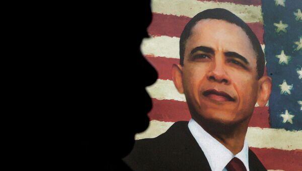 Человек на фоне портрета Барака Обамы