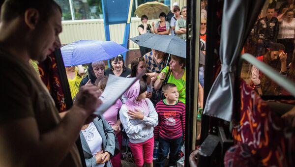 Родители с детьми во время посадки в автобусы. Архивное фото