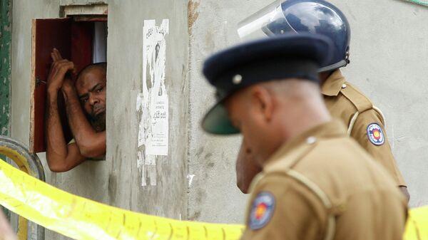 Мусульманский мужчина выглядывает из окна во время полицейского рейда в Шри-Ланке