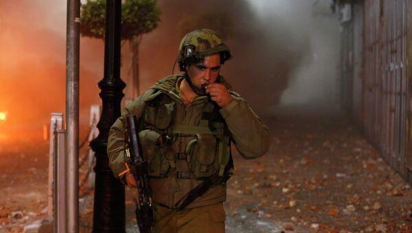 Израильский солдат после столкновений с палестинцами в Рамалле 22 июня 2014 г