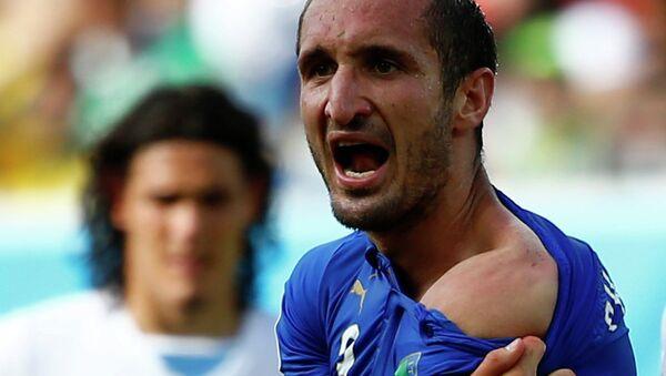 Итальянский защитник Джорджо Кьеллини показывает место, куда укусил его форвард сборной Уругвая Луис Суарес на ЧМ-2014 в Бразилии