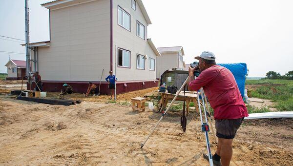 Рабочие на строительной площадке дома, построенного в рамках проекта Первого канала Всем миром