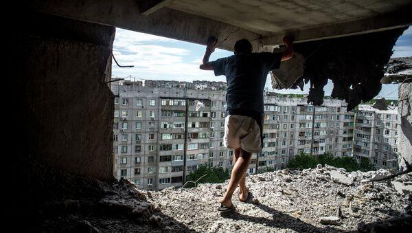 Мужчина в жилом доме, пострадавшем от артиллерийского обстрела в Луганске. Архивное фото