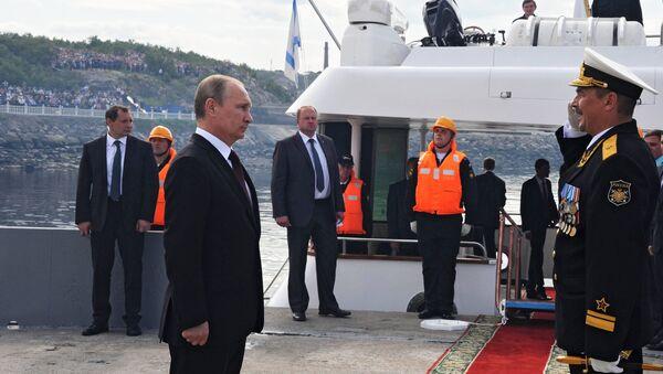 Президент России Владимир Путин (слева) принимает рапорт командующего военно-морского парада в День ВМФ в городе Североморск