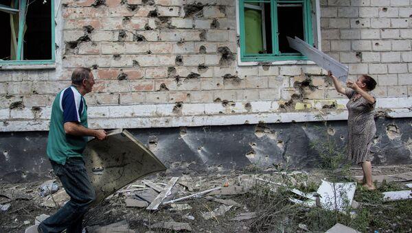 Местные жители после попадания мины во двор жилого дома во время боя в городе Шахтерск под Донецком