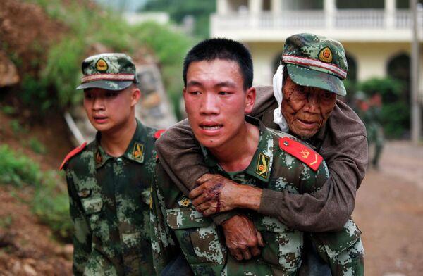 Военный медик несет раненого старика в провинции Юньнань, Китай