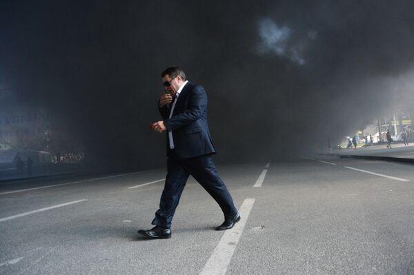 Мужчина идет мимо подожженных покрышек на площади Независимости в Киеве