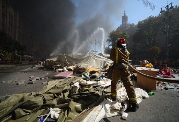 Пожарный тушит подожженные активистами покрышки на площади Независимости в Киеве