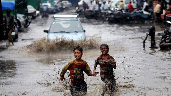 Мальчики бегут по затопленной в результате проливных дождей улице в Нью-Дели, Индия