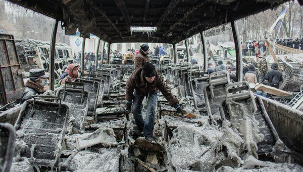Сторонники евроинтеграции Украины у выгоревшей техники на улице Грушевского в Киеве. Архивное фото.