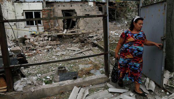 Местная жительница у жилого дома в Донецке, разрушенного при артиллерийском обстреле города украинской армией. Архивное фото