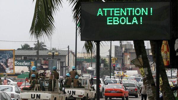 Конвой ООН проезжает мимо экрана, отображающего сообщение об Эболе на улице в Абиджане. Архивное фото
