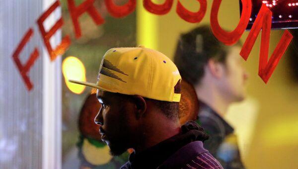 Мужчина наблюдает за беспорядками на улицах Фергюсона. Архивное фото