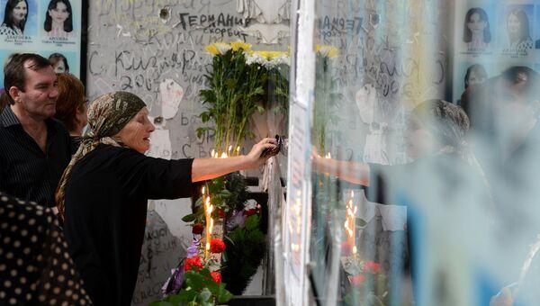 Женщина плачет на траурном мероприятии в годовщину трагедии в Беслане. Архив