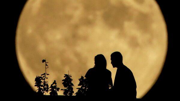 Силуэты людей на фоне луны. Архивное фото.