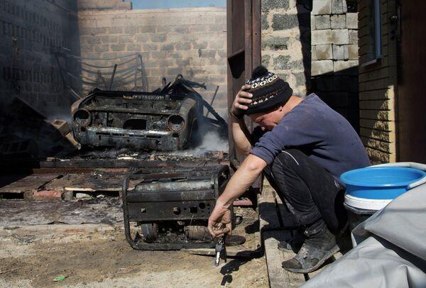 Житель Донецка возле своей сгоревшей машины и разрушенного в результате боев за аэропорт дома. 7 октября 2014