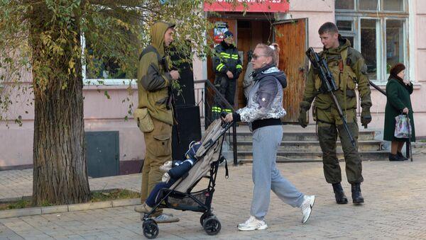 Жительница Донецка и ополченцы перед входом в избирательный участок № 125 на выборах в ДНР