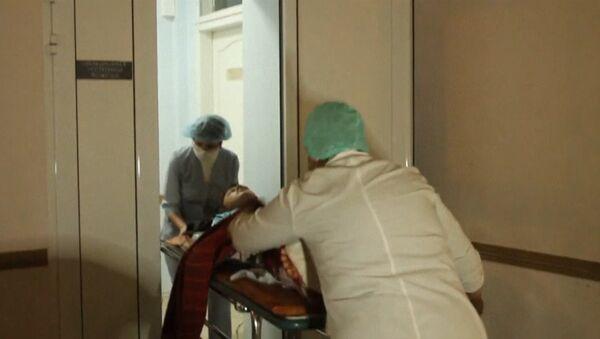 Раненного во время обстрела школы в Донецке на носилках доставили в больницу