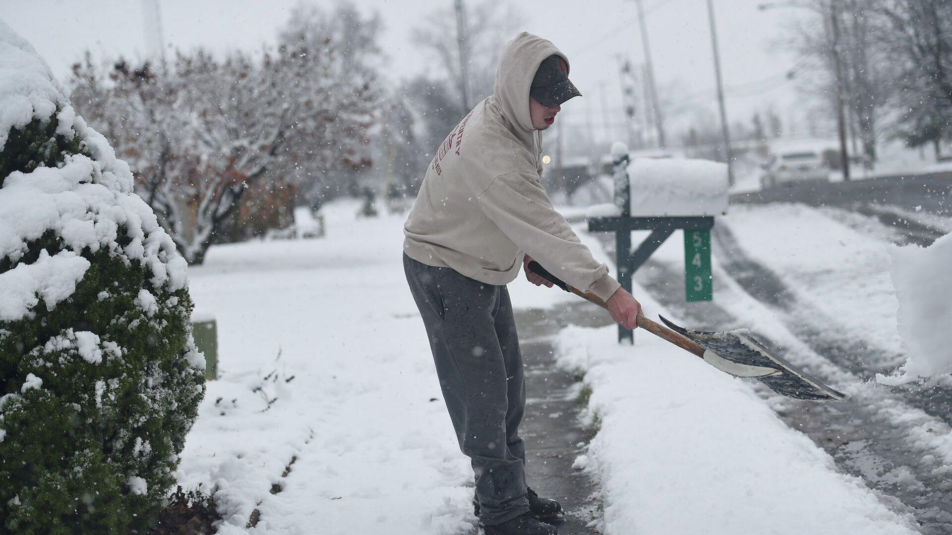 Мужчина очищает дорожку от снега в штате Пенсильвания, США. Архивное фото - РИА Новости, 1920, 04.03.2021