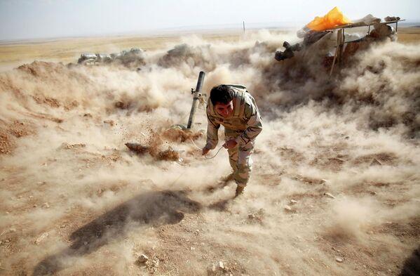 Боец из военизированного формирования Пешмерга ведет огонь по позициям ИГ возле города Мосул