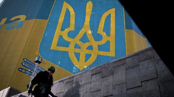Женщина проходит мимо огромного украинского флага в центре Киева. Архивное фотое