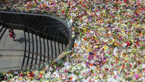 Множество цветов  в память, о погибших заложников в Сиднее