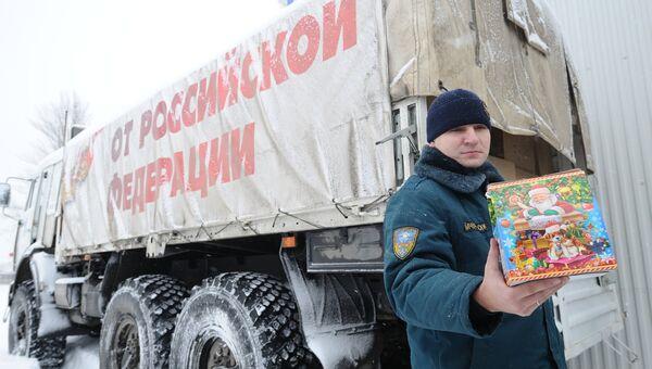 Сотрудник МЧС демонстрирует детский рождественский подарок во время формирования одиннадцатого гуманитарного конвоя для Донбасса