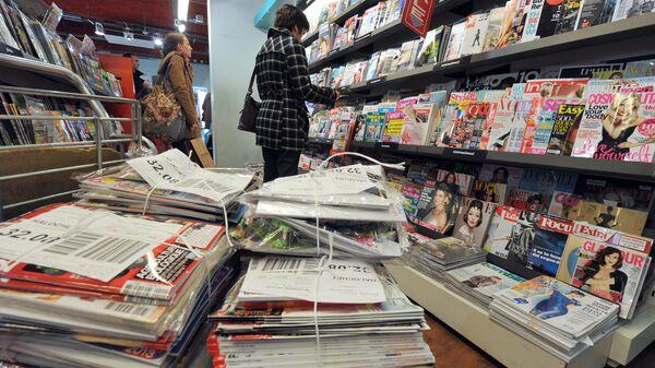 Женщина возле стенда с журналами в одном из книжных магазинов Франции. Архивное фото