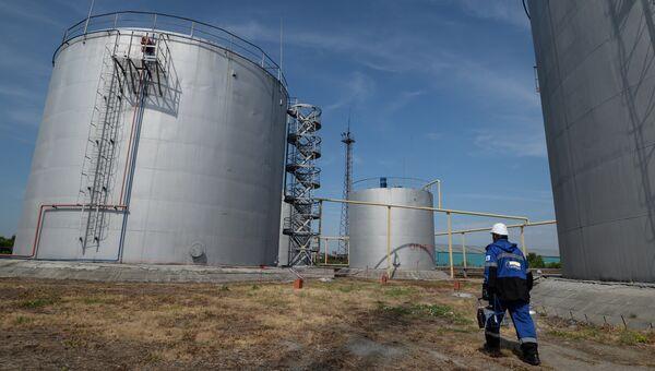 Сотрудник нефтебазы возле резервуаров для хранения топлива