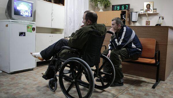 Ополченцы ДНР смотрят телевизор в холле первого военного госпиталя Донецка