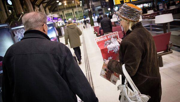 Женщина с вторым после теракта выпуском французского сатирического еженедельника Charlie Hebdo на железнодорожном вокзале в Париже. 25 февраля 2015